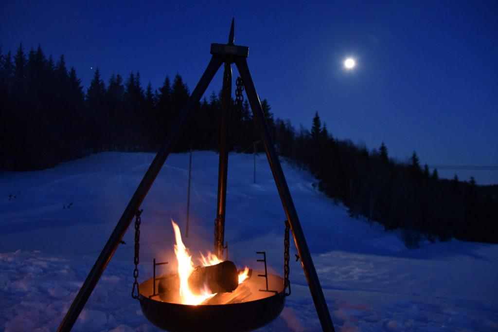 Bål, fullmåne og stjerneklar himmel.